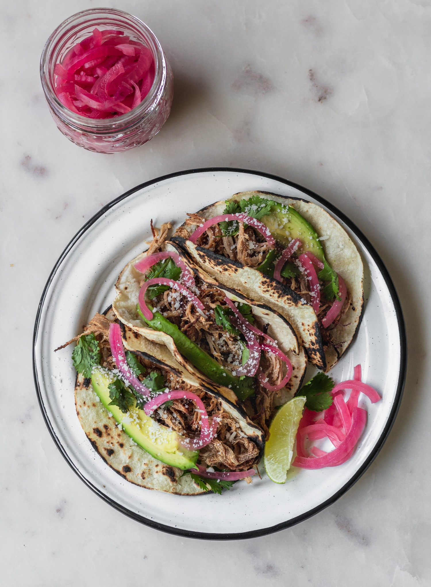 Pork tacos with blistered corn tortillas, pickled onions, and avocado.