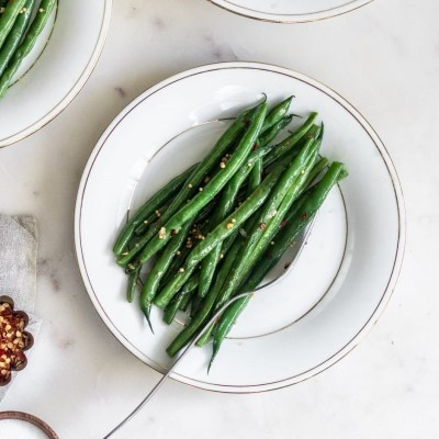 An overhead photo of green beans on a white plate surrounded by more plates on a white marble table.
