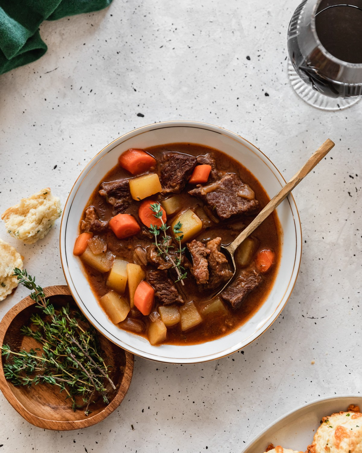 A closeup overhead image of Irish beef stew on a grey table next to a wooden bowl of thyme, a biscuit, and a glass of stout.